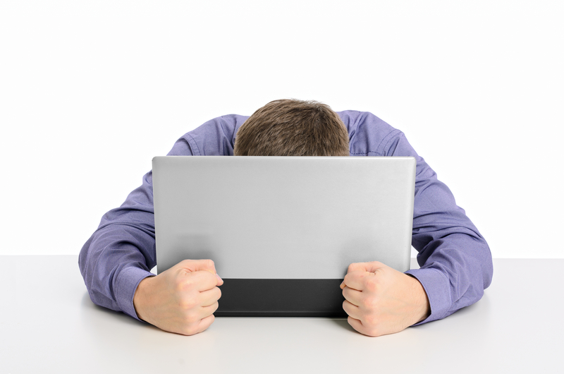 man with head on computer