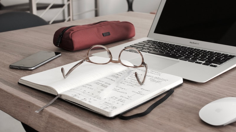 laptop on desk with notepad and glasses
