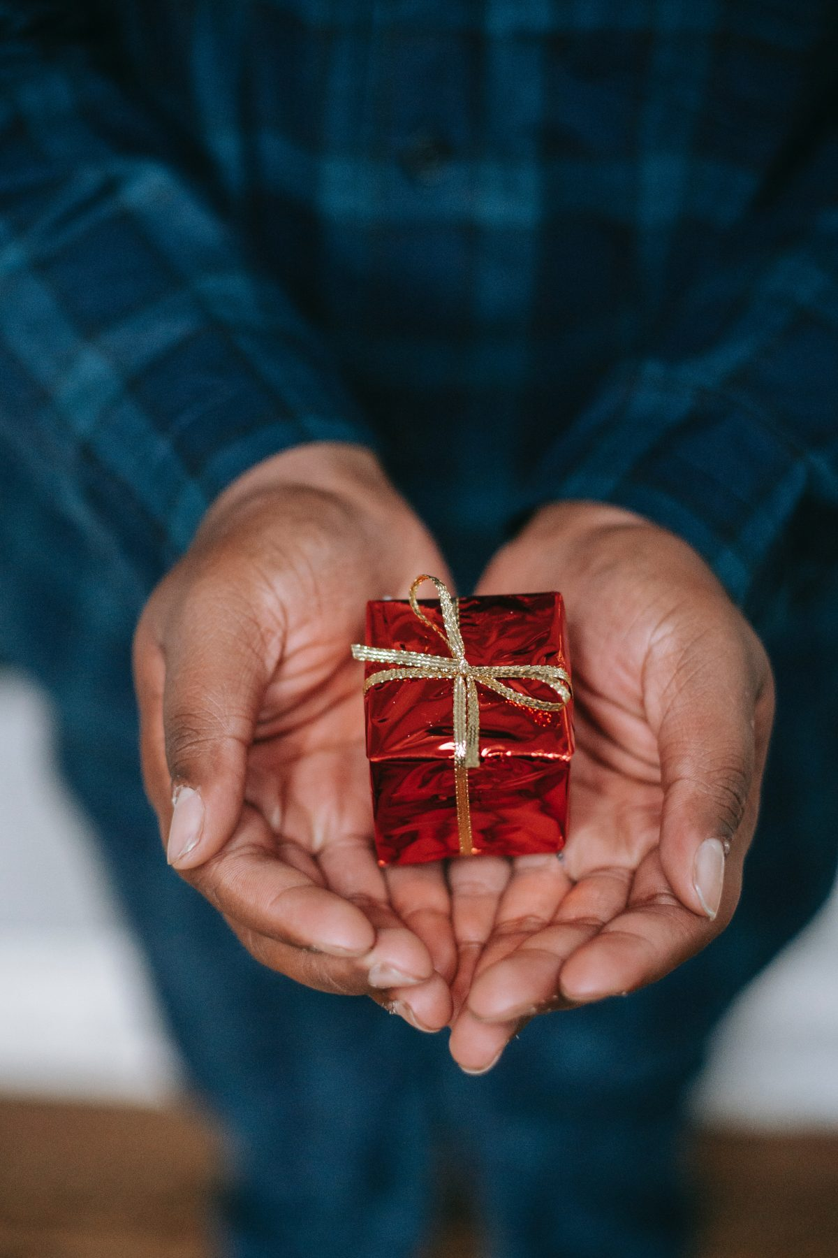 black man's hands holding red gift box
